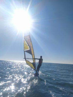 Hombre navegando en windsurf con el sol arriba. Aprendiendo en la escuela náutica