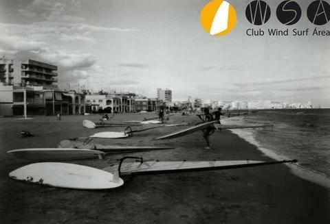 Foto en blanco y negro de playa lisa con equipos de windsurf desplegados en la arena