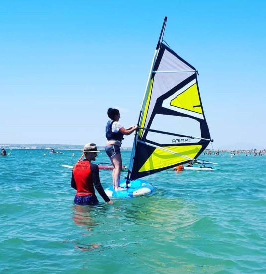 Mujer aprendiendo windsurf, con el monitor detrás indicándole