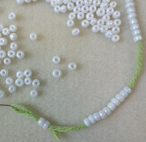 In this close-up you can see three beads singled out from the rest. Not all rocaille beads are created equal. The ones with the largest holes will slide easily onto the yarn; the others won't slide on at all. You'll get plenty of extra-large-eyed beads in a package, but more that are too-small. So, if you're planning a big project, get extra packages.