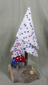 """The larger tree (""""Fourth of July"""" from the tree series) was woven using CSS. The smaller tree was woven with sport weight yarns which are not substantial enough to form a tight weave--particularly apparent in the white tier of the little tree. Also, the smaller tree was woven with the same colors but different beads. Those beads are larger than the white tree beads and I don't think they look as good."""