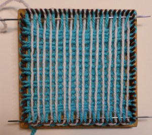 Weaving begun. Threaded needle is shown in R1 position. Unthreaded needle is shown in R16 position--it will remain there throughout the weaving process and will be used to pull the yarn through R16.