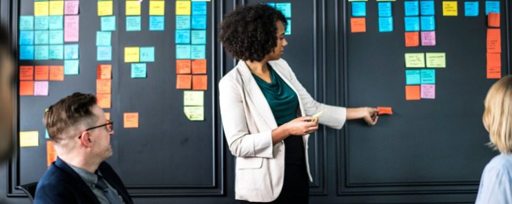 Professional woman grabbing a post-it note off of a board full of post-it notes as co-workers look on with interest.
