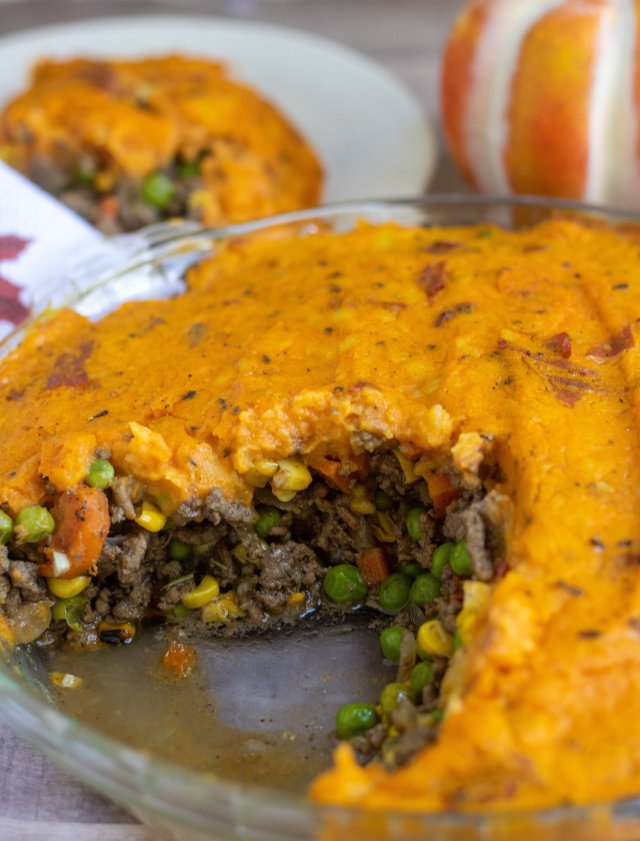 A glass pie dish filled with shepherd's pie made with fall spices and topped with rosemary brown butter pumpkin mashed potatoes.  There's a small plate in the background with a serving of the shepherd's pie and a small pumpkin in the background