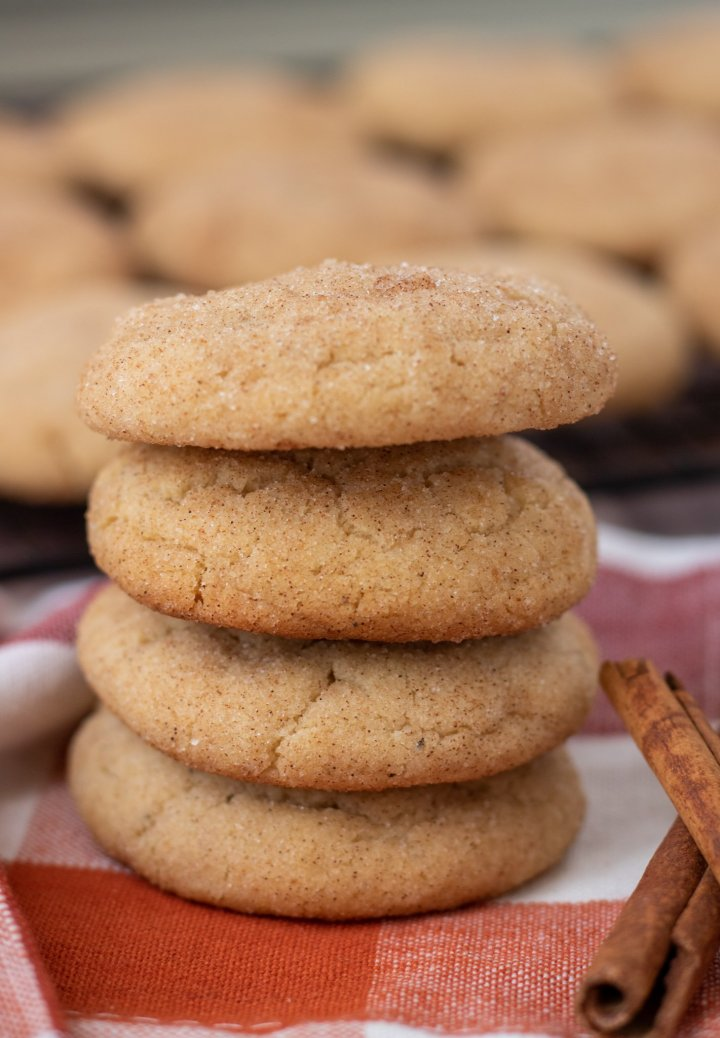4 snickerdoodle cookies stacked on top of each other. They're sitting on a orange plaid kitchen towel, with two cinnamon sticks next to them. There's a cooling rack with more cookies in the background