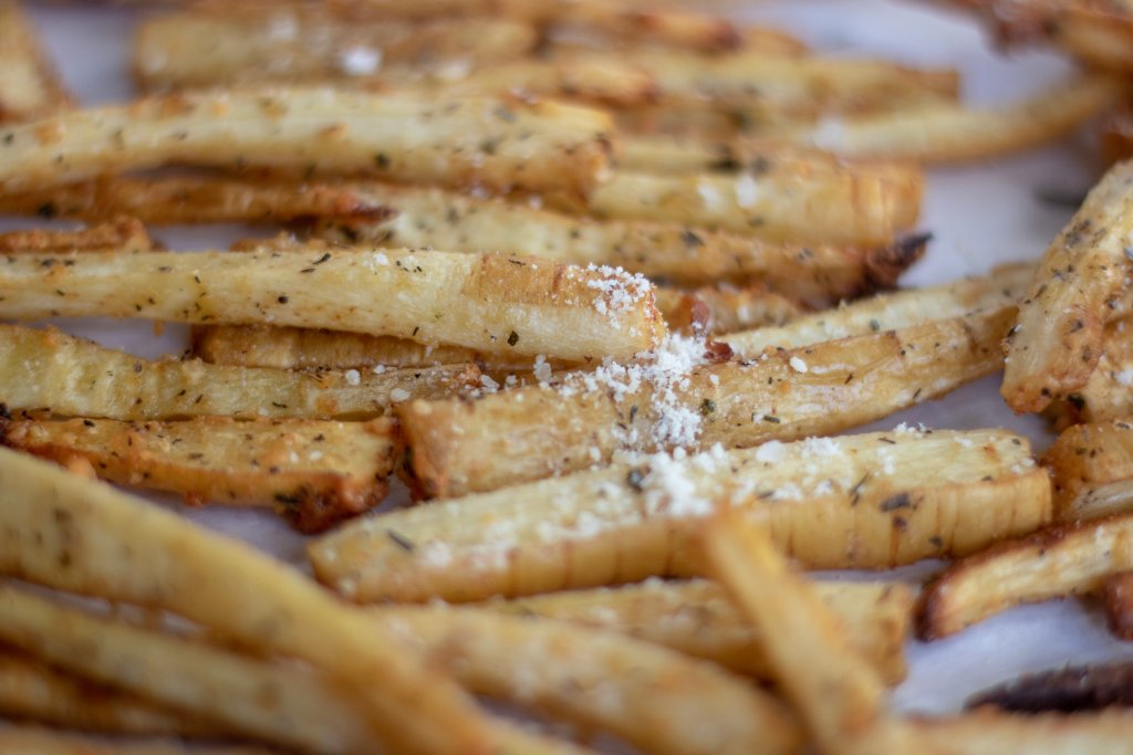 A closeup shot of crispy parsnip fries sprinkled with Parmesan and fresh rosemary