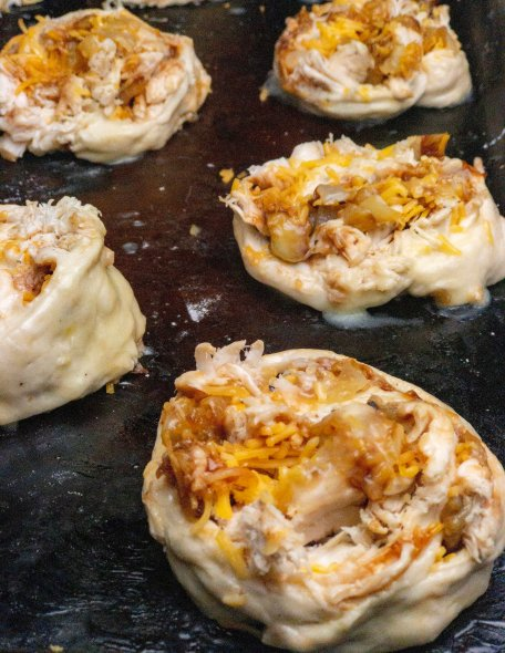 A sheet pan of unbaked barbecue chicken pizza pinwheels