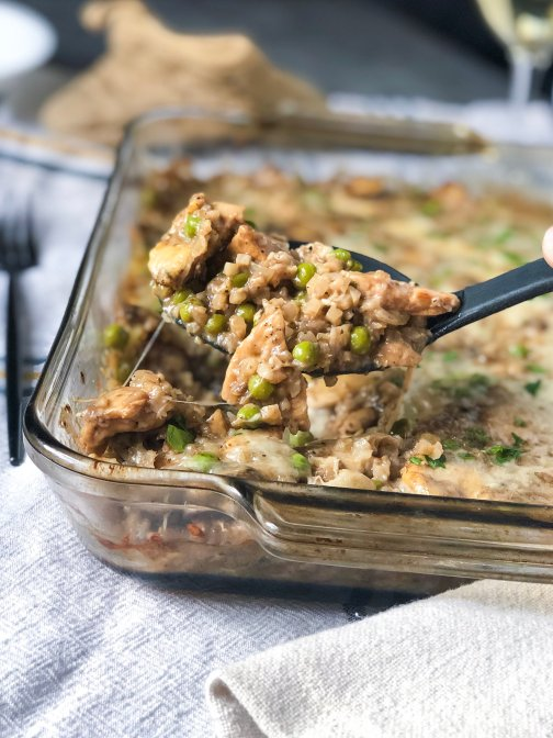 A spoonful of cheesy, creamy cauliflower rice casserole that's made with chicken, mushrooms and peas