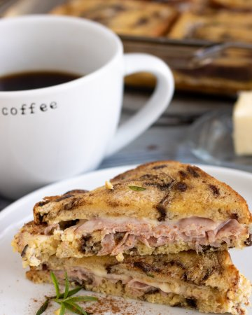 A round white dish with two halves of a ham & cheese french toast sandwich on it. The halves are cut in a triangle and there's a fresh rosemary sprig on the plate and its sprinkled with cinnamon. There's a white coffee mug with coffee in it, a glass butter dish and the rest of the casserole in the background