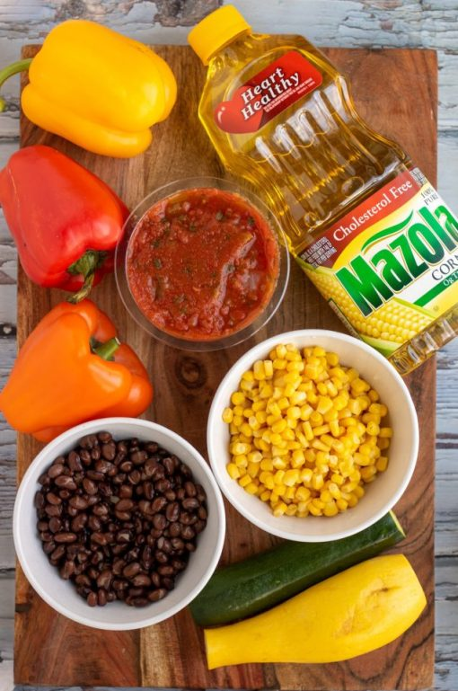 A wooden cutting board topped with an orange, yellow and red bell pepper, a white bowl full of black beans, a white bowl full of yellow corn, a container of fresh salsa, zucchini, and a whole bottle of Mazola corn oil