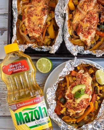A white plate topped with a foil packet filled with chicken, peppers, black beans, corn and veggies topped with greek yogurt, avocado slices and cilantro. A bottle of corn oil is next to it with half of a fresh lime There's a sheetpan in the background with more foil packet chicken.
