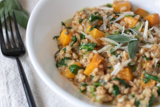A white bowl filled with creamy farro risotto with butternut squash and grated Parmesan cheese. There's a fork next to the bowl and a piece of fresh sage leaves in the background.