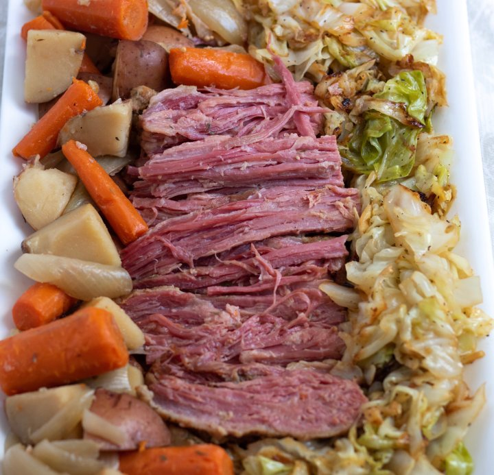 An overhead shot of a white rectangular platter filled with crockpot corned beef in the middle, potatoes, carrots and onions to the left and sautéed cabbage to the right. An easy and flavorful traditional Irish corned beef and cabbage dinner