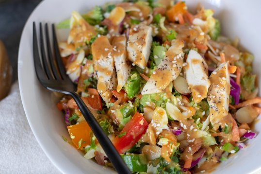 A white bowl filled with crunchy Asian salad with red peppers, cabbage, almonds, broccoli and lettuce. It's drizzled with a delicious orange sesame peanut dressing and topped with slivered almonds and sesame seeds. It's easy, healthy and low carb.