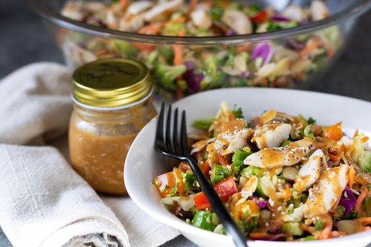 Chopped Asian salad with sesame peanut dressing and grilled chicken. A jar of Asian dressing is next to the bowl with a big bowl of salad in the background.