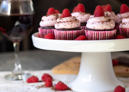 A cake stand full of chocolate cupcakes topped with raspberry whipped cream frosting and a fresh raspberry. A glass of red wine is in the background