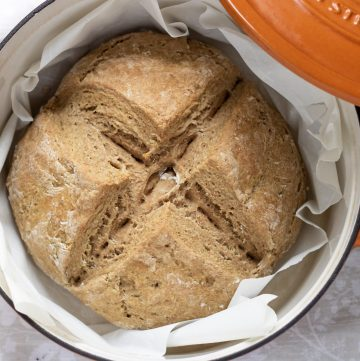 An overhead shot of a baked traditional Irish soda bread in an orange Dutch oven pan.