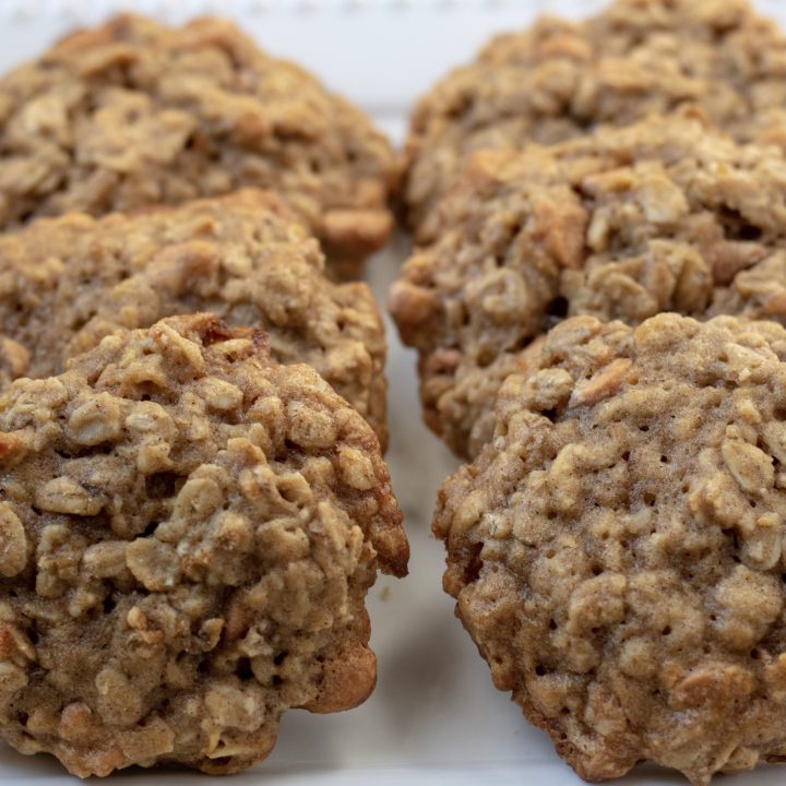 A square white dish with 6 oatmeal cookies lined up on it. They're made with cinnamon and banana.