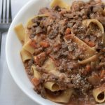 A white bowl full of vegetarian bolognese over pasta noodles. It's made with carrots, mushrooms, and eggplant
