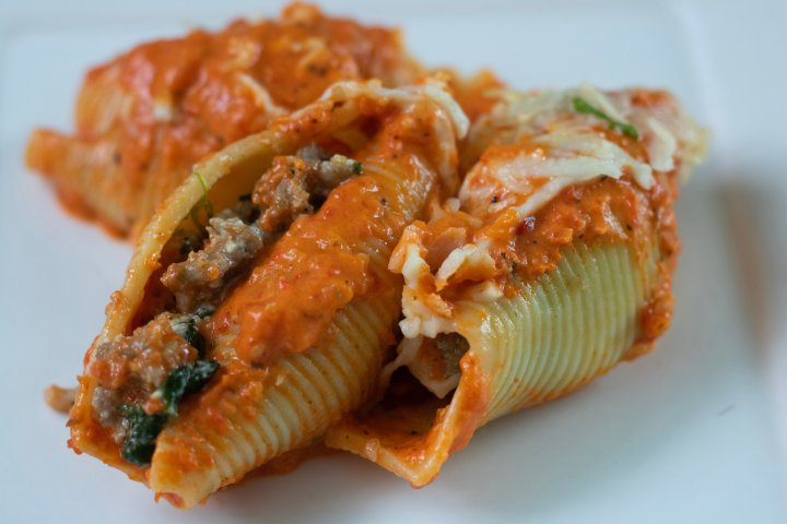 3 stuffed shells on a white plate covered in melted mozzarella cheese and filled with ricotta, sausage, spinach and goat cheese. They're topped with a roasted red pepper cream sauce.