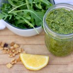 A jar of homemade pesto that's made with arugula, spinach, basil and walnuts. There's a lemon wedge, walnut pieces and a small bowl full of fresh arugula in the background