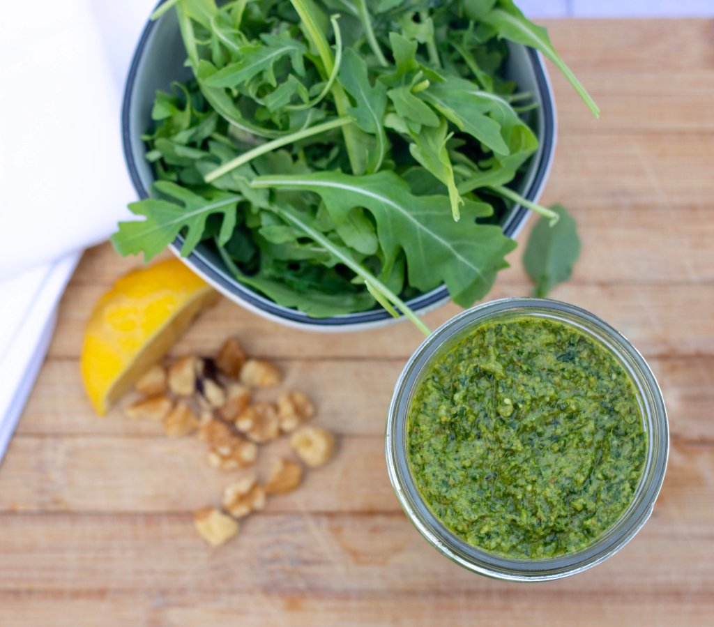 An overhead shot of arugula pesto, walnuts, lemon and fresh arugula. The pesto is easily made in the food processor and can be used in fish, chicken, pasta or pizza.