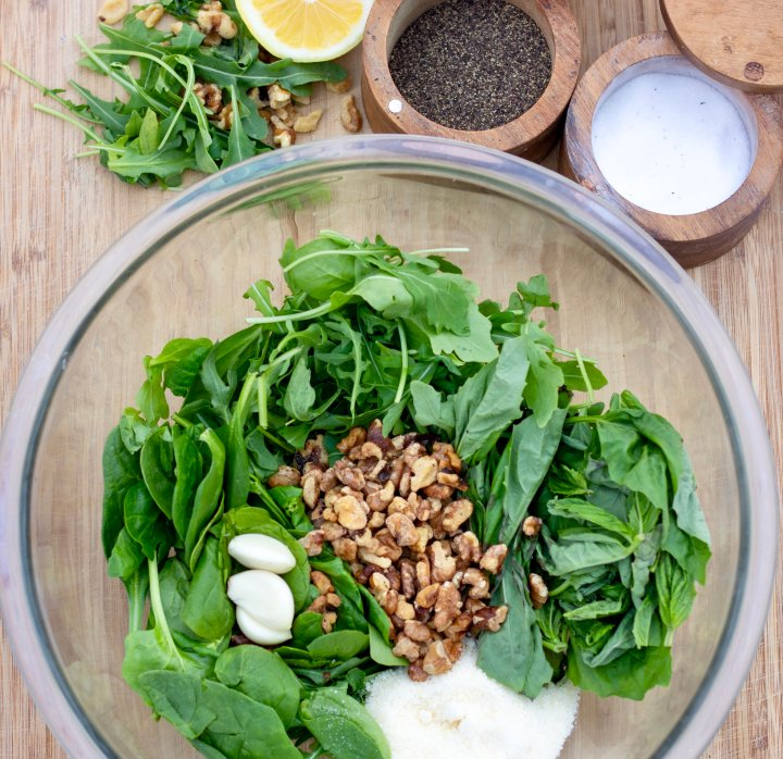 A round clear bowl filled with fresh arugula, basil, spinach, garlic cloves and Parmesan cheese. Salt, pepper, lemon and olive oil is added slowly and blended until the pesto sauce is smooth.