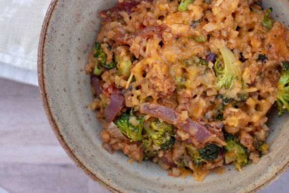 A bowl full of cheesy, low carb cauliflower rice casserole that's made with chicken, broccoli and BBQ sauce