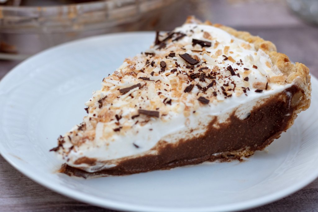 A slice of chocolate coconut cream pie in a white plate. There's toasted coconut and shaved chocolate sprinkled on the top