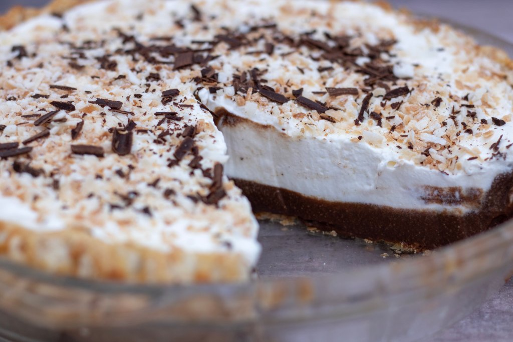 A whole chocolate coconut cream pie with a slice taken out. You can see the creamy homemade chocolate filling inside that's topped with whipped cream and toasted coconut