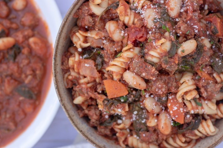A bowl full of an easy pasta dish thats made from tomato sauce, ground turkey, spinach and white beans. It's an easy and tasty family dinner recipe.