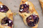 A puff pastry square is filled with blueberry filling, a slice of prosciutto and goat cheese crumbles. The two corners are folded over each other to create a pouch. It's baked until golden and flaky and drizzled with honey thyme.