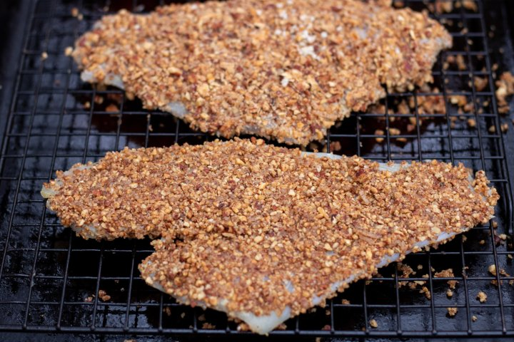 Pieces of white fish crusted with toasted pecans and placed on a baking sheet to be baked in the oven.