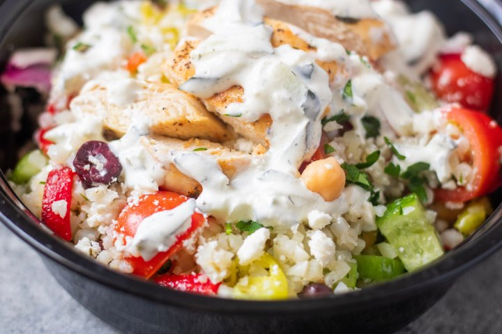 A bowl of cauliflower rice packed with Greek chicken, peppers, onions, chickpeas, tomatoes and cucumbers and topped with tzatziki sauce. A healthy meal prep recipe idea.