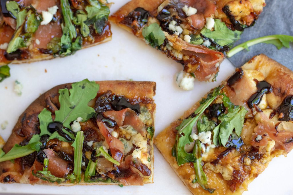 Cut up square pieces of flatbread pizza topped with arugula, prosciutto, blue cheese crumbles and fig Jam. The prosciutto is slightly crispy and it's finished with a balsamic drizzle
