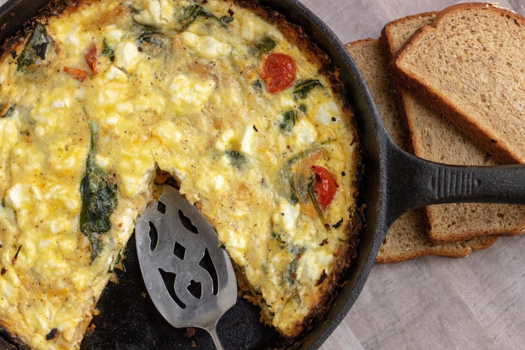 A black cast iron pan filled with quiche. It's got a slice missing with a pie serving utensil. You can see the roasted tomatoes, goat cheese & spinach in the quiche. A couple slices of whole grain bread sit next to it.