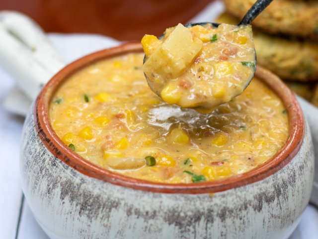 A bowl full of fresh corn chowder with a spoonful taken out of it. The spoon has chunks of yellow potatoes and zucchini and the chowder is thick and creamy.