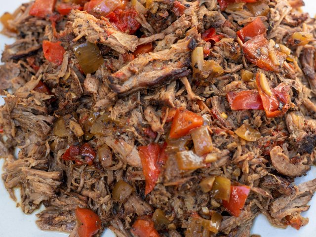 a while bowl full of tender shredded crockpot chipotle barbacoa taco meat. It's got chopped red bell peppers and onions mixed it. It's slightly browned and very tender.