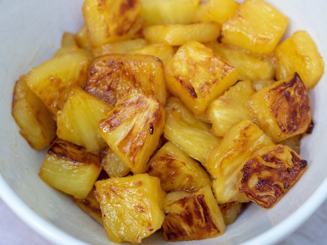 A white bowl of pineapple chunks that have been caramelized with brown sugar until golden.