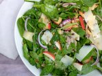 A large white bowl of spinach salad with farro, pine nuts, shaved parmesan, sliced apples, red onions and a honey dijon dressing.