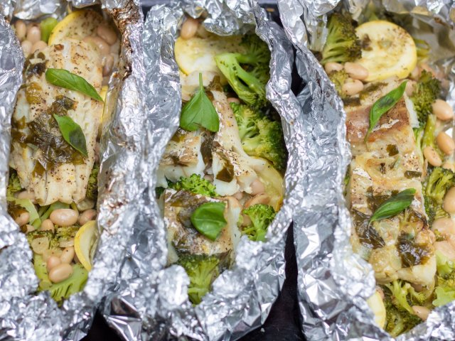 3 foil packets filled with white fish and vegetables like broccoli and yellow summer squash. It's topped with fresh basil and a lemon garlic butter sauce.