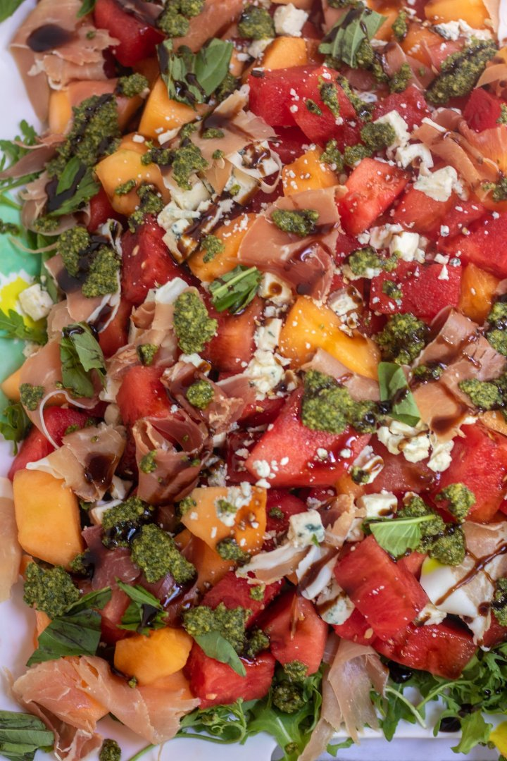 A bed of arugula topped with chunks of watermelon, cantaloupe, prosciutto & Gorgonzola cheese crumbles. It's topped with mint basil pesto and balsamic drizzle.
