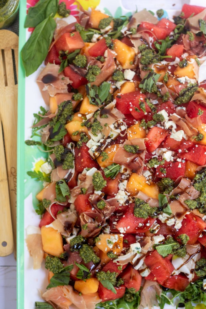A large rectangle platter topped with summer melon salad with prosciutto, Gorgonzola cheese crumbles. It's drizzle with balsamic glaze and dollops of basil mint pesto.