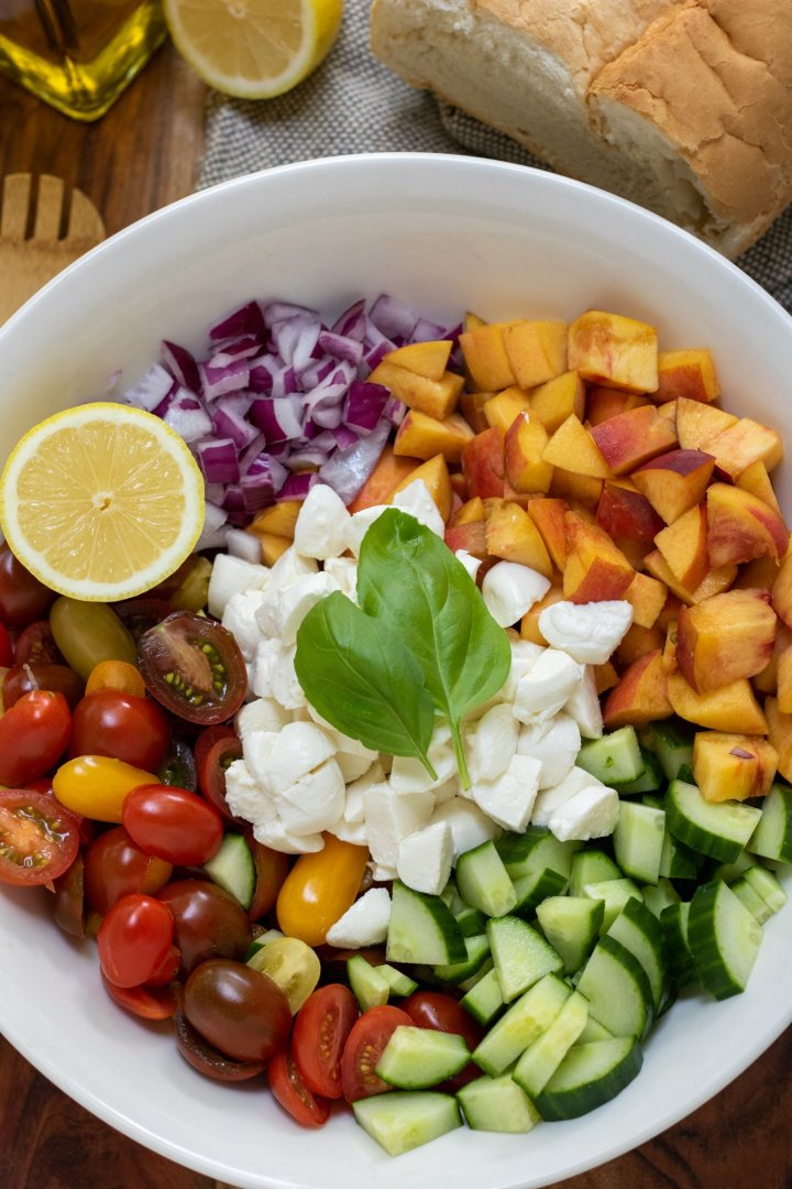 A large white bowl with halved cherry tomatoes, diced cucumber, red onion, diced peaches, a half a lemon, & fresh basil leaves. There's a loaf of Italian bread in the background with a wooden serving spoon and olive oil