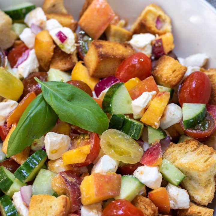 A large white bowl with chunks of golden crispy bread, cherry tomatoes, cucumbers, red onion slices, fresh basil, mozzarella and peaches.