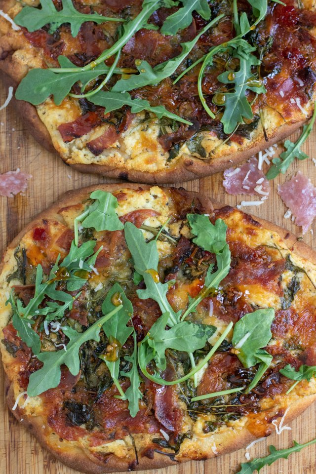 A wooden cutting board with 2 flatbread pizzas that are crispy and golden brown. They're topped with slices of salami, ricotta and goat cheese, arugula and drizzled with red pepper jelly. There's shredded cheese and arugula sprinkled on the cutting board and slices of fresh salami.