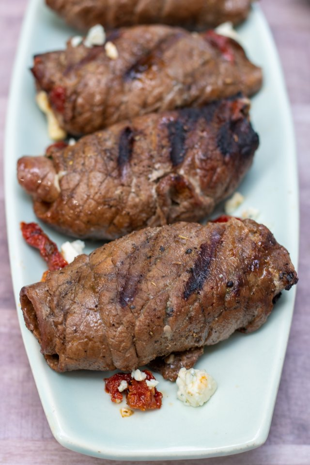 a light blue, oblong serving platter with 3 steak roll ups that have slight char marks and are browned. There's some gorgonzola crumbles on the platter and some sun dried tomatoes.