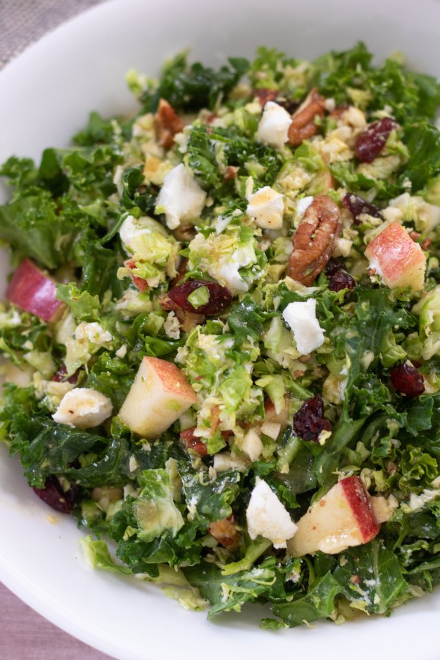 An up close shot of shredded brussels sprout and kale salad. It's topped with toasted pecans, goat cheese and apples and tossed with a maple dijon dressing.