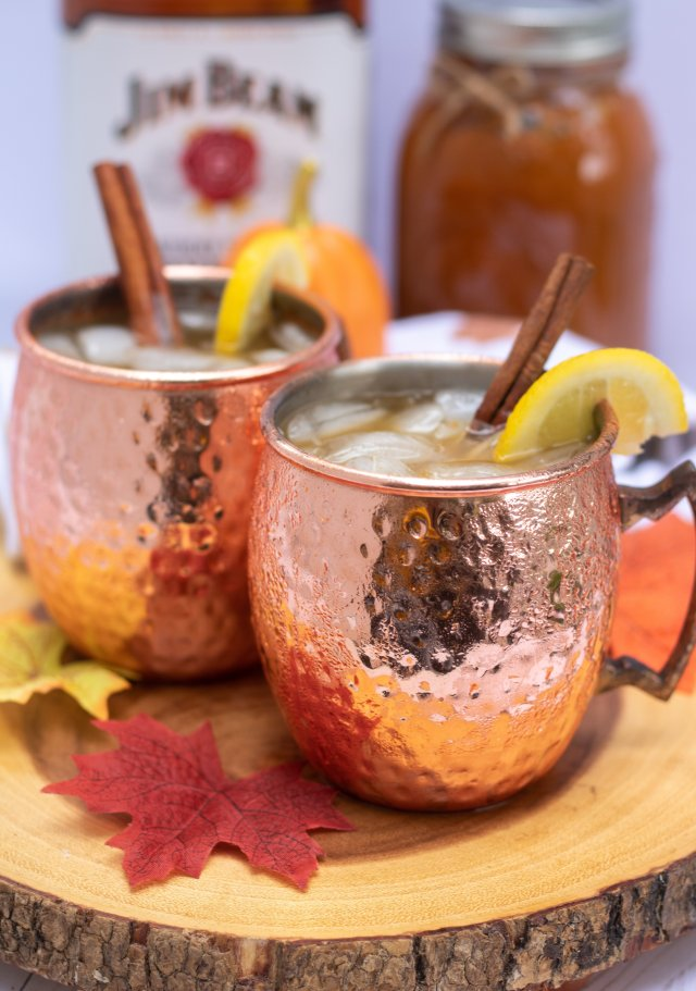 Two copper mugs on a wood slice with ice in them and a lemon wedge and cinnamon stick. They're made with pumpkin butter you can see the mason jar in the background. You can see the bark on the wood slice with a red fall leaf.