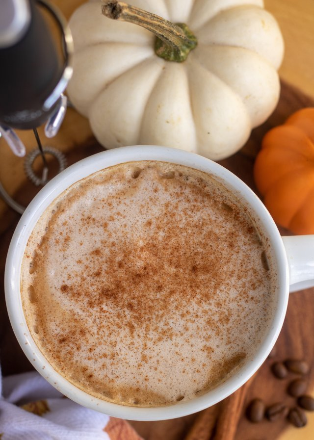 A white coffee mug with pumpkin latte sprinkled with cinnamon. It's on a wooden circle with a small white and orange pumpkin